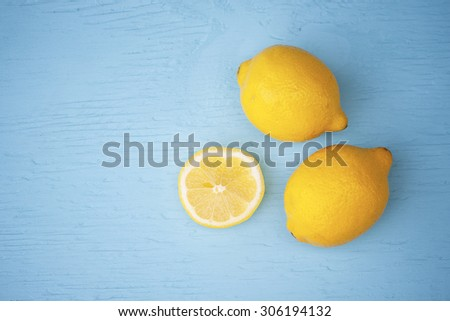 Macro view of vibrant, yellow lemon slice and two whole lemons on rustic, wooden teal table background, shallow DOF - stock photo