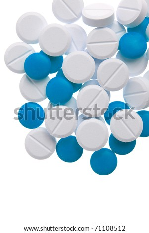 Macro view of white and blue pills on blue background. - stock photo