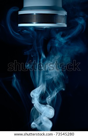 Macro view of wispy smoke around white fire sensor or smoke detector, dark background. - stock photo