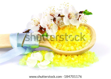 Macro view of wooden spoon with yellow bath salt and white flowers isolated on white background - stock photo