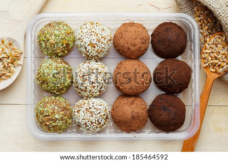 macrobiotic healthy food: balls from ground wheat sprouts with sesame, pumpkin seeds and chocolate sprinkles in plastic box; sprouted grains in wooden spoon on table, top view - stock photo