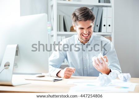 Mad annoyed young businessman working and crumpling paper in office - stock photo