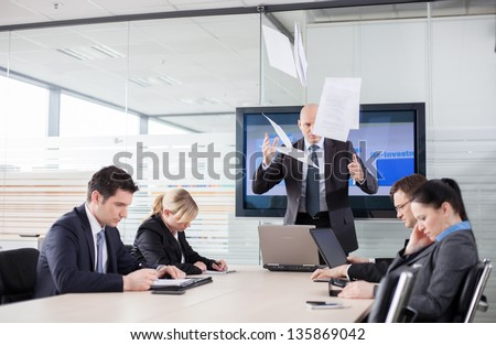 Mad CEO throwing documents at a meeting. Subordinates looking down, afraid to make eye contact. - stock photo