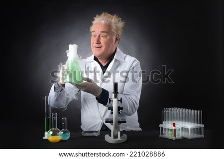 mad clinician studies in laboratory and holding flask. surprised man standing on black background at table with microscope - stock photo