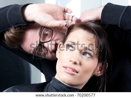 Mad hairdresser with a terrified customer. In a hair salon. Selective focus. - stock photo