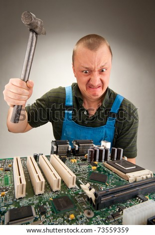 Mad IT worker repairing computer circuits by hammer - stock photo