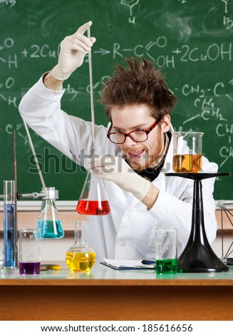 Mad professor adds something to the Erlenmeyer flask with red water - stock photo
