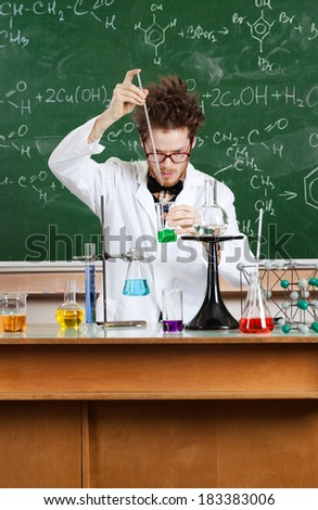 Mad professor conducts some chemical experiments in his laboratory - stock photo