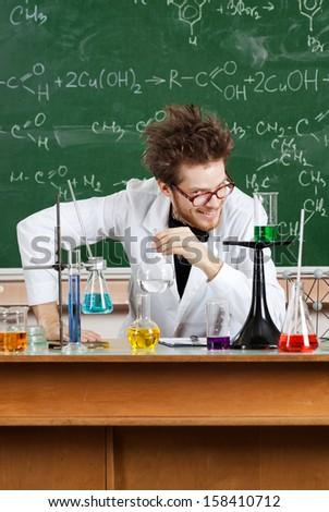 Mad professor laughs in his laboratory - stock photo