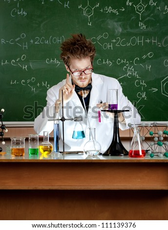Mad professor shows attention gesture in his laboratory - stock photo