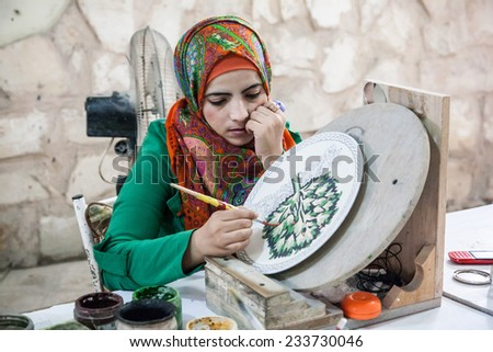 MADABA, JORDAN, NOVEMBER 16 2013, Woman is making Mosaic Painting on the plate. - stock photo