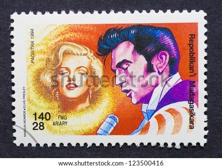 MADAGASCAR - CIRCA 1994: a postage stamp printed in Madagascar showing an image of Elvis Presley and Marilyn Monroe, circa 1994. - stock photo