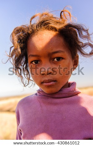 MADAGASCAR - JULY 3, 2011: Portrait of an unidentified beautiful girl in a violet jacket in Madagascar, July 3, 2011. Children of Madagascar suffer of poverty due to the unstable situation.