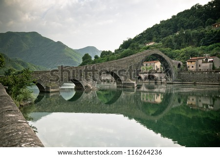 Maddalena Bridge at Bagni di Lucca, Tuscany, Italy. Also known as the Devil's Bridge. Toned and vignetted image. - stock photo