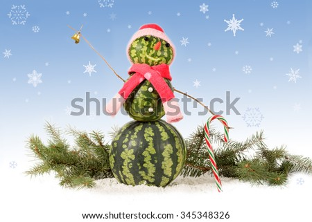 made from watermelon Snowman  in red hat and scarf with candy cane on blue background and falling snowflakes. Holiday concept for New Years. - stock photo