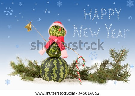 made from watermelon Snowman  in red hat and scarf with candy cane on blue background and falling snowflakes. Holiday concept for New Years with  inscription - stock photo