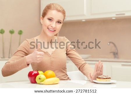 Made the right choice. Young lady sits at the table showing thumb up because she has strong will to decline eating donut and prefers apples and oranges