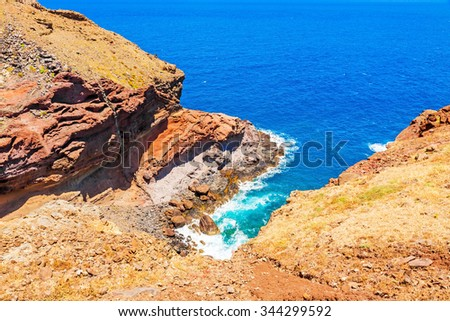 Madeira - colorful cliff coast, rocks at bay with surge of waves of the Atlantic Ocean