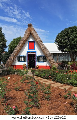 Madeira Island, the city Santana. Cosy chalet with a triangular thatched roof. Before the house - garden with beautiful flower beds. - stock photo