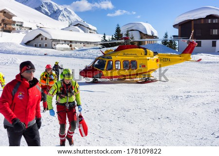 MADESIMO - FEBRUARY 22: Rescue helicopter evacuates skier after accident, Madesimo, Italy on February 22, 2014. - stock photo