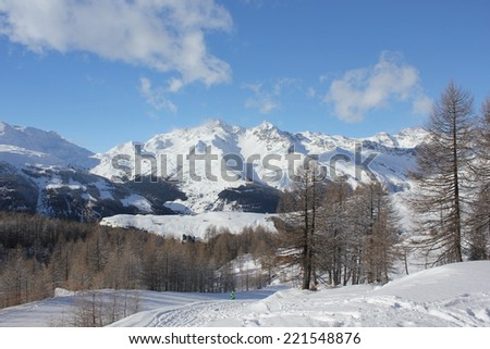 Madesimo, Italy, december 26, 2012: Sunny day in Italy Winter season. Tree branches and ski piste covered with snow, with the mountain in the background