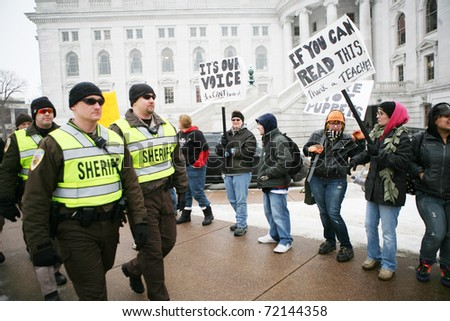 MADISON, WI-FEB 21:Deputies walk past protesters who form a circle around the capitol building February 21, 2011 in Madison, Wisconsin. - stock photo