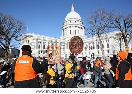 MADISON, WI-FEB 19: Opponents of Gov Scott Walker's bill to take away the bargaining rights of public workers march on the capitol square on February 19, 2011 in Madison, Wisconsin. - stock photo