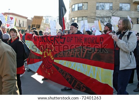 MADISON, WI - FEB 19: Unidentified people protest WI Budget Repair Bill on February 19, 2011 on the capitol square in Madison, Wisconsin.  The protesters hold a banner demonstrating solidarity. - stock photo