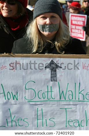 MADISON, WI - FEB 19: Unidentified woman protests WI Budget Repair Bill on February 19, 2011 on the capitol square in Madison, WI.  The woman wears tape on her mouth representing having no voice. - stock photo