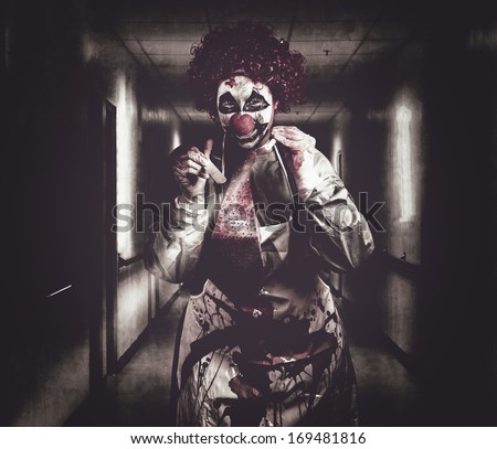 Madness the creepy medical clown standing in grunge hospital hallway with flashlight and tongue prong. Terminal treatment - stock photo