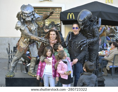 Madrid-8 December.  Happy unknown family with children posing for photo with heroes of pictures in the street-on 8 December 2014 in Madrid - stock photo