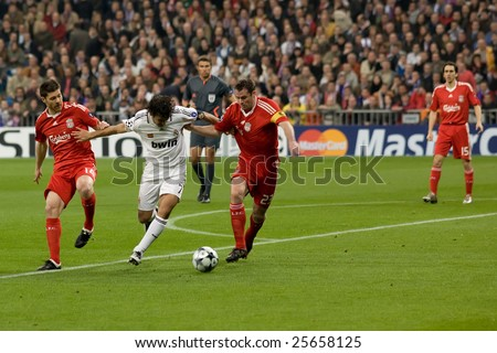 MADRID - FEB 25: Real Madrid player Raul Gonzalez fights off Liverpool players Jamie Carragher and Xabi Alonso during their Champions League second round matchon February 25, 2009 in Madrid. - stock photo