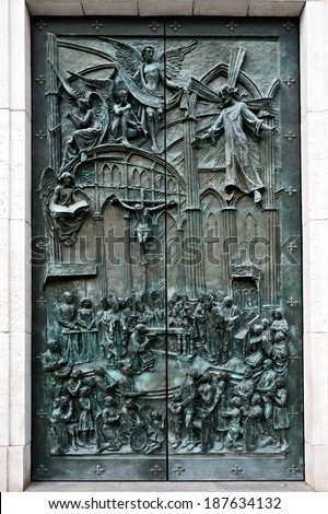 MADRID - MAR 3, 2014:  Bas-relief on the door of neo-gothic of Santa Maria la Real de La Almudena - famous cathedral in Madrid, Spain. It was consecrated by Pope John Paul II in 1993