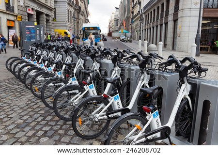 MADRID - OCTOBER 10: Bikes parked on the sidewalk, belonging to Madrid public system (BiciMad) on October 10, 2014 in Madrid Spain.  - stock photo