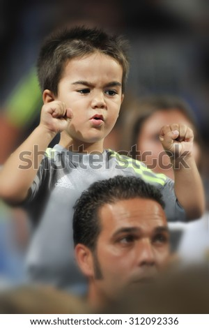 MADRID, SPAIN -  August 29th, 2015 :  small child fan of REAL MADRID excited cheering passionate seating on shoulders of his father during La Liga match vs BETIS at Santiago Bernabeu Stadium - stock photo