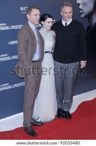 MADRID, SPAIN - JANUARY 04: Actor Daniel Craig, actress Rooney Mara and director David Fincher attend 'The Girl With The Dragon Tattoo' premiere at Callao cinema on January 4, 2012 in Madrid, Spain. - stock photo