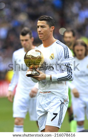 MADRID, SPAIN - January 25th, 2014 : Portuguese CRISTIANO RONALDO of REAL MADRID holds Ballon Dor 2013 FIFA Award (Ball of Gold) as best player of the world at Santiago Bernabeu Stadium. - stock photo