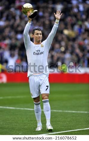 MADRID, SPAIN - January 25th, 2014 : Portuguese CRISTIANO RONALDO of REAL MADRID holds Ballon Dor 2013 FIFA Award (Ball of Gold) as best player of the world at Santiago Bernabeu Stadium. - stock photo