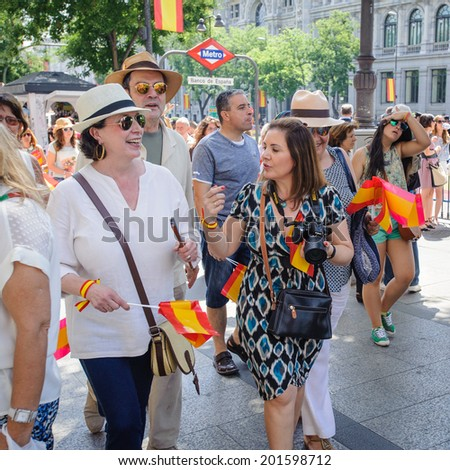 MADRID, SPAIN - JUN 19, 2014: Unidentified Spanish people with national flags walk in the centre of Madrid on a case of the celebration on a day of the inauguration of the New King of Spain Felipe IV