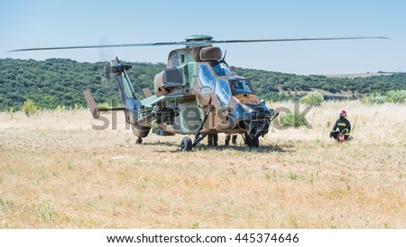 MADRID, SPAIN - JUNE 23, 2016: A fully armed Spanish Army Eurocopter Tiger helicopter landed on open field, keeping engines on while refueling (part of units 50th anniversary). Firefighter nearby