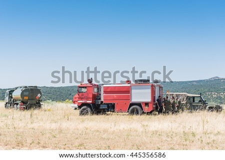 MADRID, SPAIN - JUNE 23, 2016: A Spanish Army fuel tank, fire truck and military transport at an open field ready to conduct helicopter refueling operations during a maneuver.