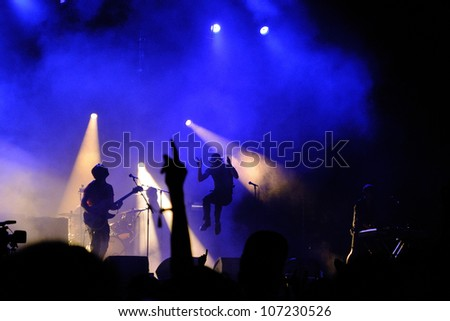 MADRID, SPAIN - JUNE 23: Silhouette of Paul Smith, singer of Maximo Park (band), jumping during his concert at Matadero de Madrid on June 23, 2012 in Madrid, Spain. Dia de la Musica Festival. - stock photo