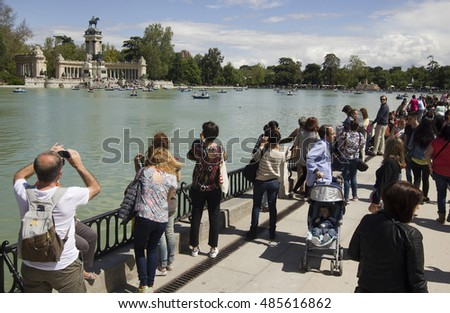 Madrid, Spain - May 29, 2016: People take pictures and admire the view of the pond of the public El Retiro park in Madrid, Spain on May 29, 2016