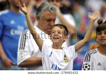 MADRID, SPAIN - May 13th, 2015 :  young kid fan of REAL MADRID cheering the team excited during Europe Champions League match VS JUVENTUS at Santiago Bernabeu Stadium - stock photo