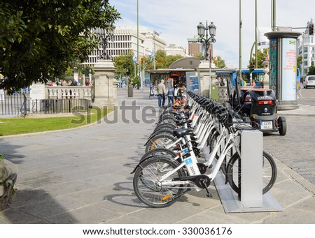 Madrid, Spain - October 21, 2015: Two workers realize works of maintenance in the bicycles of rent of Madrid - stock photo