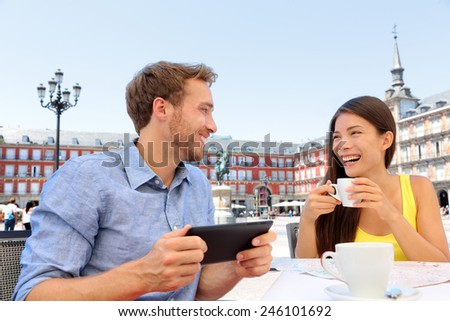 Madrid tourists at cafe drinking coffee having fun using tablet travel app on Plaza Mayor. Tourist couple sightseeing visiting tourism landmarks and attractions in Spain. Young woman and man - stock photo