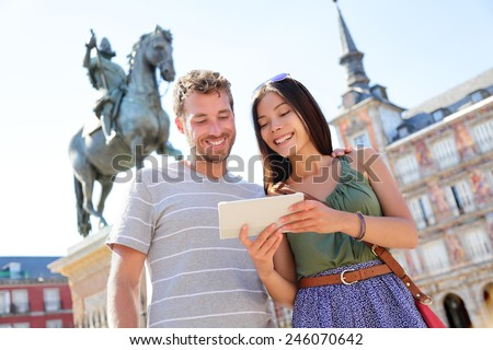 Madrid tourists using tablet travel app guidebook ebook on Plaza Mayor by statue of King Philip III. Tourist couple sightseeing visiting tourism landmarks and attractions in Spain. Young woman and man - stock photo