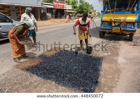 Madurai, India - October 18, 2013: A crew of two men and one woman repair the road in Madurai. Dirt and stones to fill the lowness in the road and then liquid tar to cover it. - stock photo