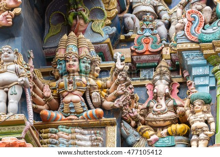Madurai, India - October 19, 2013: Closeup of goddess Gayatri sitting on coffin with the four Vedas inside. Ganesha keeps her company. Facade of West Gopuram at Meenakshi Temple.