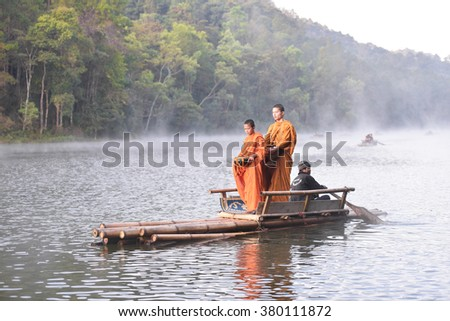 Mae Hong Son, Thailand February 21,2016:Monks and Tourists get on a Bamboo raft for sightseeing around to Pang Ung reservoir lake view beautiful mountain scenes, and hazy fog in the morning.
